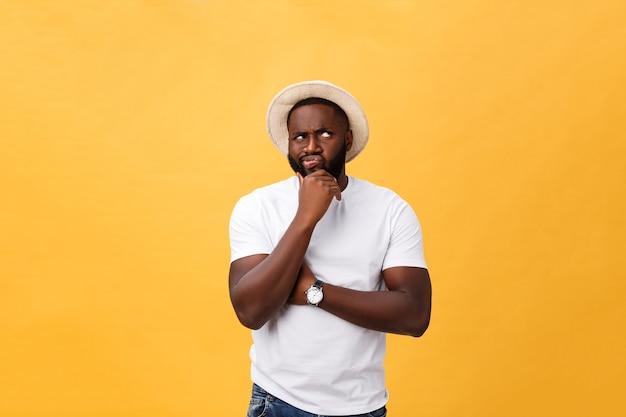 Jonge afro-amerikaanse man opzoeken met doordachte en sceptische uitdrukking, vinger op zijn kin, in een poging zich iets te herinneren.