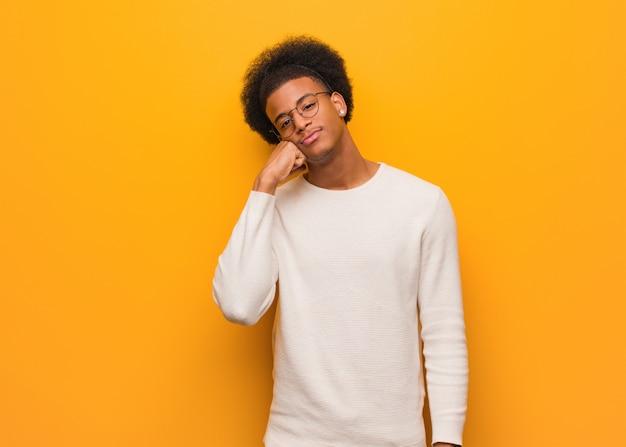 Jonge afro-amerikaanse man over een oranje muur denken aan iets, op zoek naar de kant