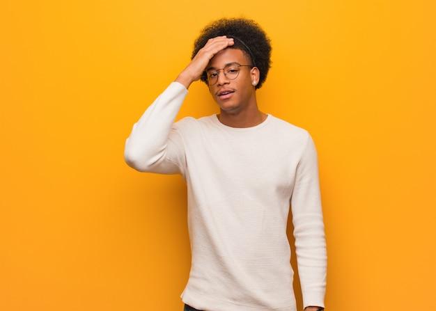 Jonge afro-amerikaanse man over een oranje muur moe en erg slaperig