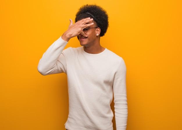 Jonge afro-amerikaanse man over een oranje muur pijnlijk en lachen op hetzelfde moment