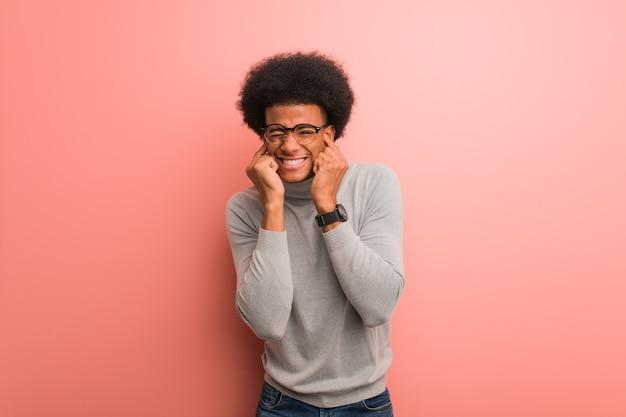 Jonge afro-amerikaanse man over een roze muur die oren bedekt met handen