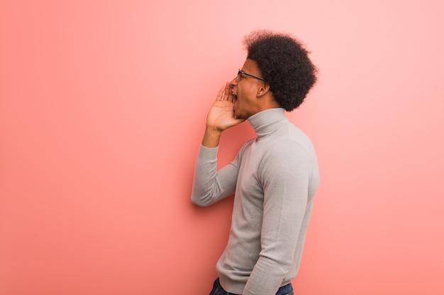 Jonge afro-amerikaanse man over een roze muur fluisteren roddel ondertoon
