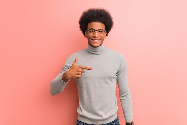 Jonge afro-amerikaanse man over een roze muur persoon wijst met de hand naar een shirt kopie ruimte, trots en zelfverzekerd