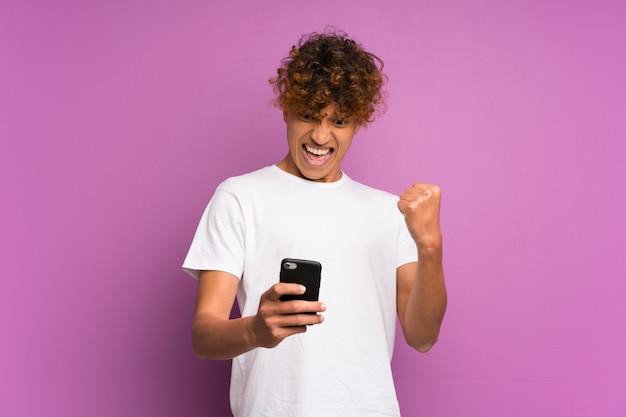 Jonge afro-amerikaanse man over geïsoleerde paarse muur met telefoon in de overwinningspositie