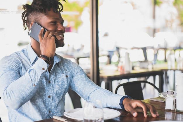 Jonge afro-amerikaanse man praten aan de telefoon terwijl hij in een restaurant zit.
