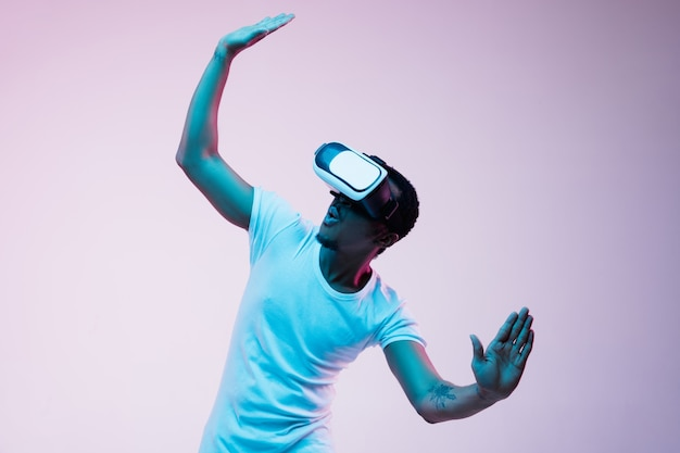 Jonge afro-amerikaanse man speelt en gebruikt vr-bril in neonlicht op achtergrond met kleurovergang