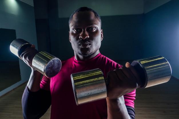 Jonge afro-amerikaanse man sportman gehurkte sportman uitoefening halter t-shirt sport uniformen sport dragen zwarte achtergrond studio gym