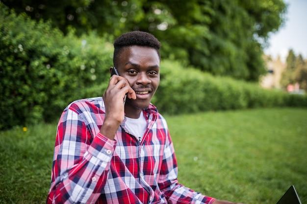 Jonge afro-amerikaanse man spreekt aan de telefoon zittend op het groene gras met laptop