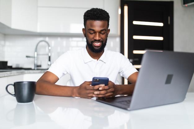 Jonge afro-amerikaanse man telefoon gebruiken zittend met laptop in de keuken