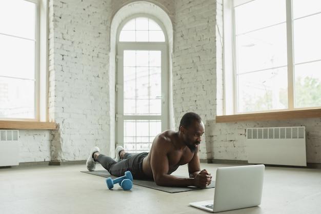 Jonge afro-amerikaanse man traint thuis tijdens quarantaine van uitbraak van coronavirus, doinc-oefeningen van fitness, aerobic. sportief blijven tijdens isolatie. wellness, bewegingsconcept. plank.