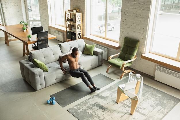 Jonge afro-amerikaanse man traint thuis tijdens quarantaine van uitbraak van coronavirus, doinc-oefeningen van fitness, aerobic. sportief blijven tijdens isolatie. wellness, bewegingsconcept. sit ups.