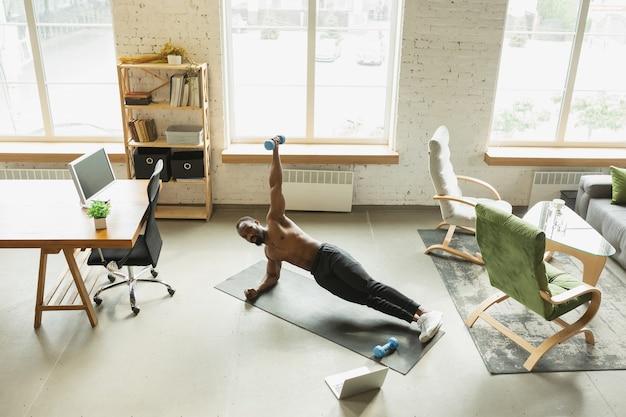 Jonge afro-amerikaanse man traint thuis tijdens quarantaine van uitbraak van coronavirus, doinc-oefeningen van fitness, aerobic. sportief blijven tijdens isolatie. wellness, bewegingsconcept. zijplank.