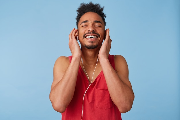 Jonge afro-amerikaanse man voelt zich geweldig en erg gelukkig, sluit de ogen en geniet, luistert met een koptelefoon naar zijn favoriete liedje, houdt zijn hoofd schuin en glimlacht breed geïsoleerd.