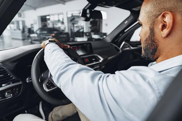 Jonge afro-amerikaanse man zit in een nieuwe auto in de autoshowroom en binnen rondkijken