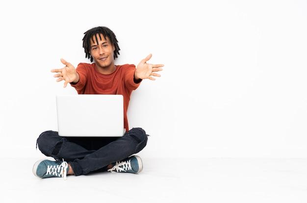 Jonge afro-amerikaanse man zittend op de vloer en werken met zijn laptop presenteren en uitnodigen om met de hand te komen