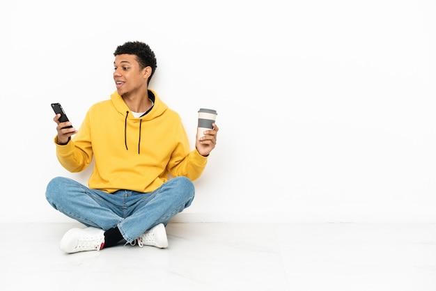 Jonge afro-amerikaanse man zittend op de vloer geïsoleerd op een witte achtergrond met koffie om mee te nemen en een mobiel
