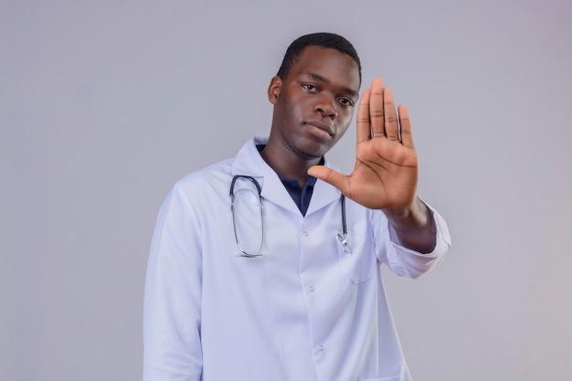 Jonge afro-amerikaanse mannelijke arts dragen witte jas met een stethoscoop met ernstig gezicht met open hand stopbord maken