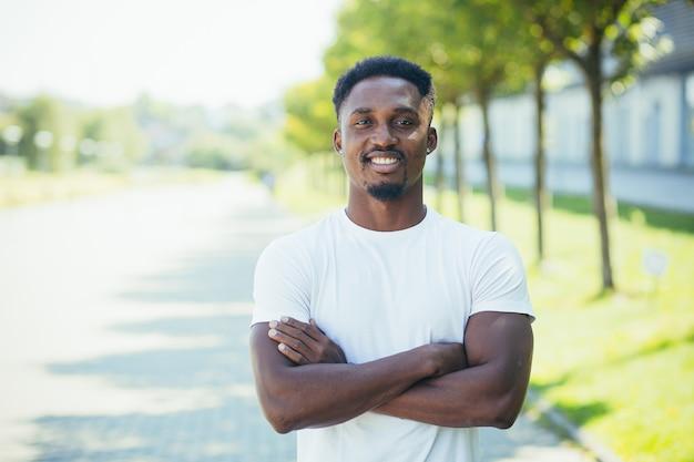 Jonge afro-amerikaanse mannelijke atleet, op een ochtend joggen, kijkt naar de camera met zijn armen gekruist, gemotiveerd en glimlachend