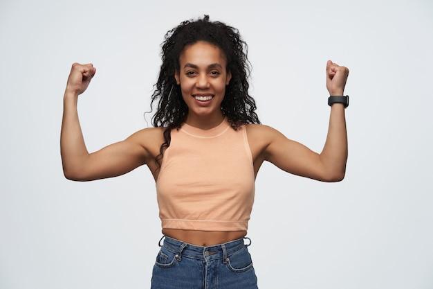 Jonge afro-amerikaanse meid lacht breed en laat haar spieren zien