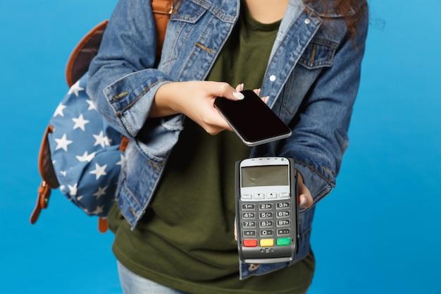 Jonge afro-amerikaanse meisje tiener student in denim kleding, rugzak houd terminal geïsoleerd op blauwe muur
