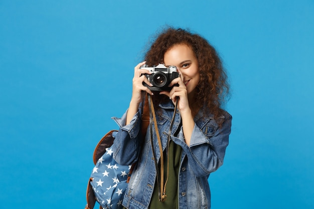 Jonge afro-amerikaanse meisje tiener student in denim kleding rugzak houden camera geïsoleerd op blauwe muur