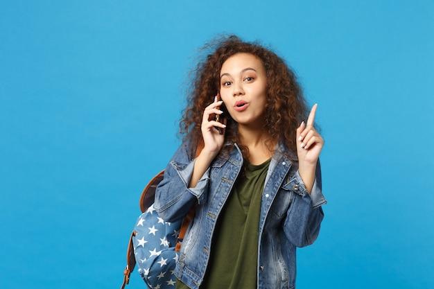 Jonge afro-amerikaanse meisje tiener student in denim kleding, rugzak houden telefoon geïsoleerd op blauwe muur