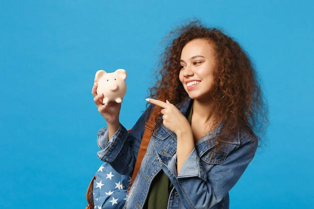 Jonge afro-amerikaanse meisje tiener student in denim kleding, rugzak houden varken geïsoleerd op blauwe muur