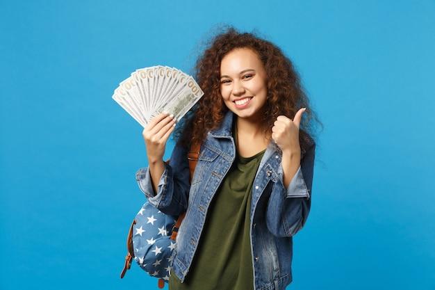 Jonge afro-amerikaanse meisje tiener student in denim kleding, rugzak houdt contant geld geïsoleerd op blauwe muur