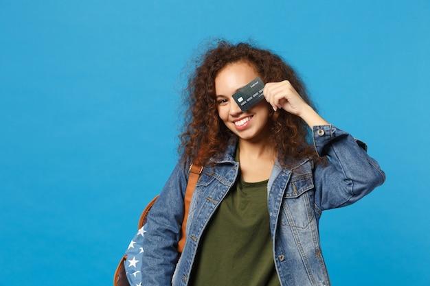 Jonge afro-amerikaanse meisje tiener student in denim kleding, rugzak houdt creditcard geïsoleerd op blauwe muur