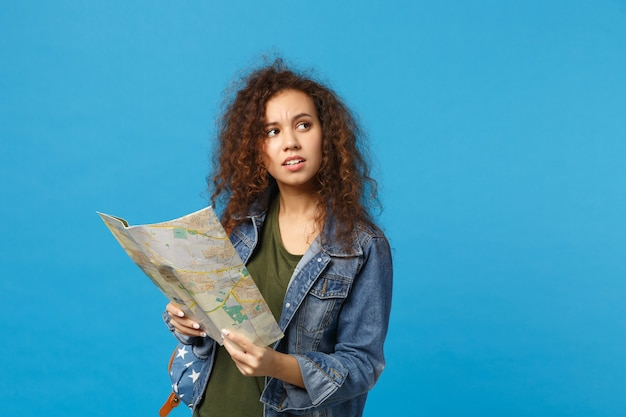 Jonge afro-amerikaanse meisje tiener student in denim kleding, rugzak houdt kaart geïsoleerd op blauwe muur