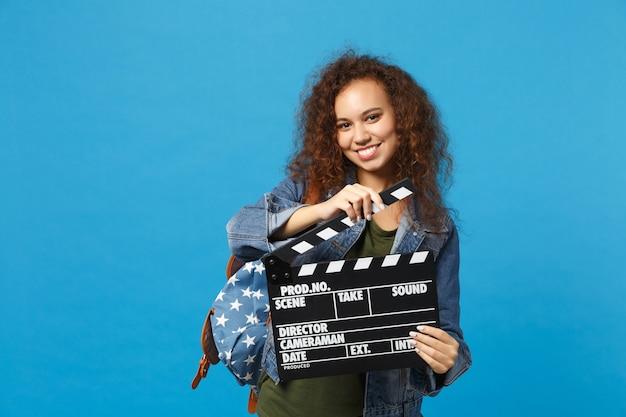 Jonge afro-amerikaanse meisje tiener student in denim kleding, rugzak houdt klepel geïsoleerd op blauwe muur