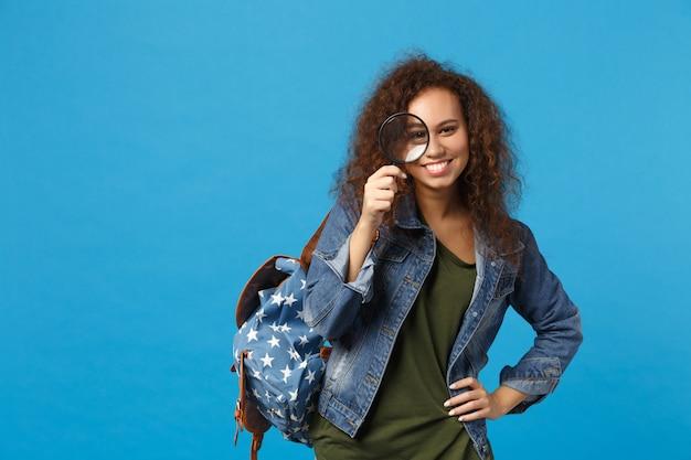 Jonge afro-amerikaanse meisje tiener student in denim kleding, rugzak houdt klok geïsoleerd op blauwe muur