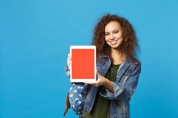 Jonge afro-amerikaanse meisje tiener student in denim kleding, rugzak houdt pad pc geïsoleerd op blauwe muur muur
