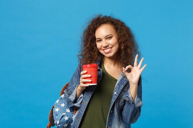 Jonge afro-amerikaanse meisje tiener student in denim kleding, rugzak houdt papieren beker geïsoleerd op blauwe muur