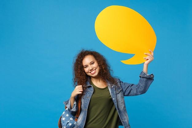 Jonge afro-amerikaanse meisje tiener student in denim kleding, rugzak houdt zeggen wolk geïsoleerd op blauwe muur