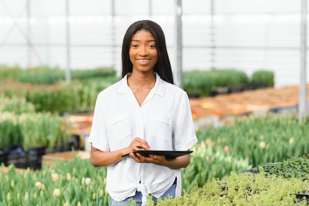 Jonge afro-amerikaanse meisje, werknemer met bloemen in kas.