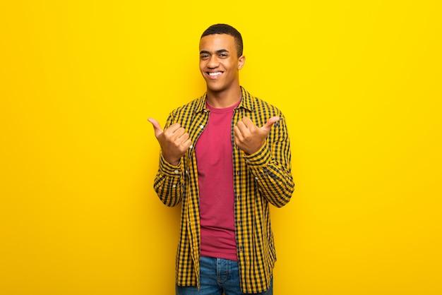 Jonge afro amerikaanse mens die op gele achtergrond duimen op gebaar met beide handen en het glimlachen geeft
