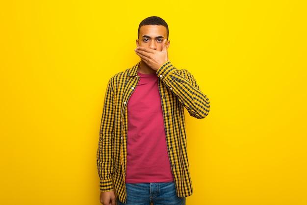 Jonge afro amerikaanse mens op gele achtergrond die mond behandelen met handen voor iets ongepast zeggen