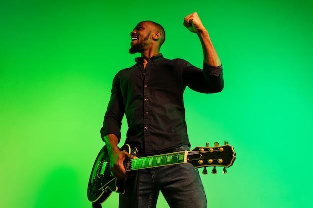 Jonge afro-amerikaanse muzikant die gitaar speelt als een rockster op een groen-gele achtergrond met kleurovergang. concept van muziek, hobby, festival, openlucht. vrolijke man improviseren, zingen lied.
