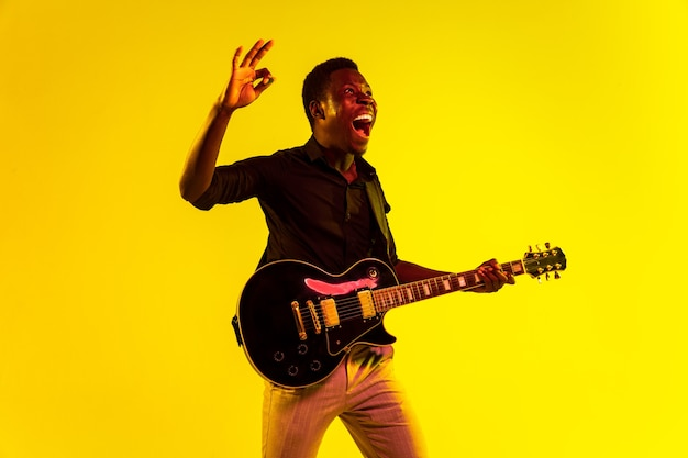 Jonge afro-amerikaanse muzikant die gitaar speelt als een rockster op gele achtergrond in neonlicht. concept van muziek, hobby, festival, openlucht. vrolijke man improviseren, zingen lied.