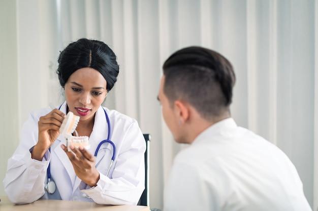 Jonge afro-amerikaanse of zwarte tandartsvrouw met kunstgebit met een blij gezicht glimlachend