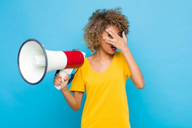 Jonge afro-amerikaanse op zoek geschokt, bang of doodsbang, die gezicht bedekt met hand en gluren tussen vingers met een megafoon
