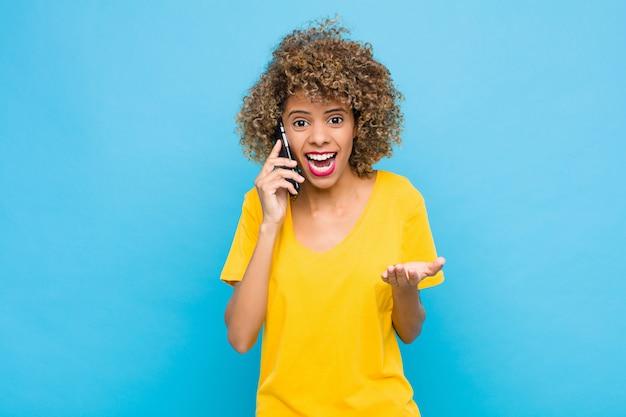 Jonge afro-amerikaanse op zoek wanhopig en gefrustreerd, gestrest, ongelukkig en geïrriteerd, schreeuwen en schreeuwen met een mobiele telefoon