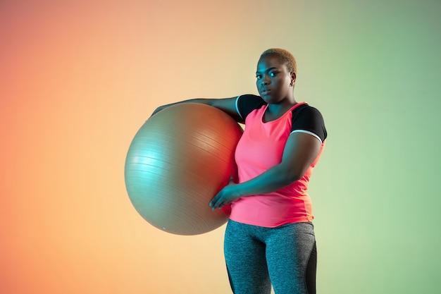 Jonge afro-amerikaanse plus size vrouwelijke model training op gradiënt muur in neonlicht.