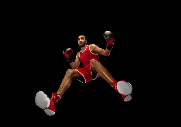 Jonge afro-amerikaanse professionele bokser in actie, beweging geïsoleerd op zwarte muur, kijk vanaf de onderkant. concept van sport, beweging, energie en dynamische, gezonde levensstijl. trainen, oefenen.