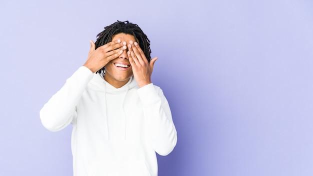 Jonge afro-amerikaanse rasta man bedekt ogen met handen, glimlacht in het algemeen wachtend op een verrassing.