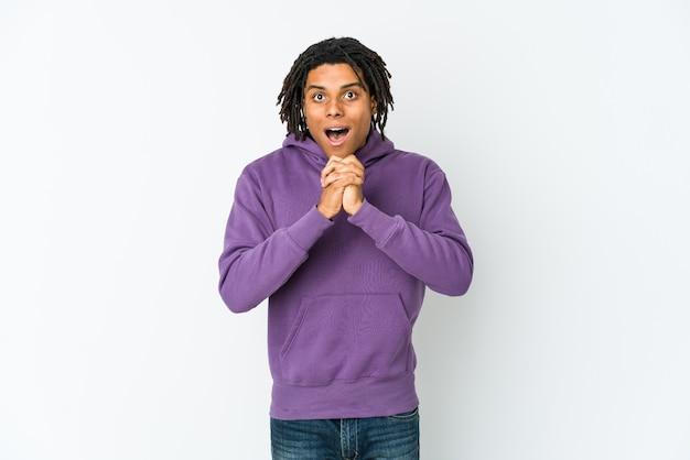 Jonge afro-amerikaanse rasta man bidden voor geluk, verbaasd en mond openen op zoek naar voren.