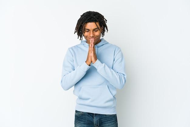 Jonge afro-amerikaanse rasta man hand in hand bidden in de buurt van mond, voelt zich zelfverzekerd.