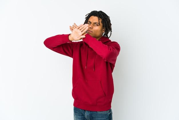 Jonge afro-amerikaanse rastaman die twee armen gekruist houdt, ontkenningsconcept.