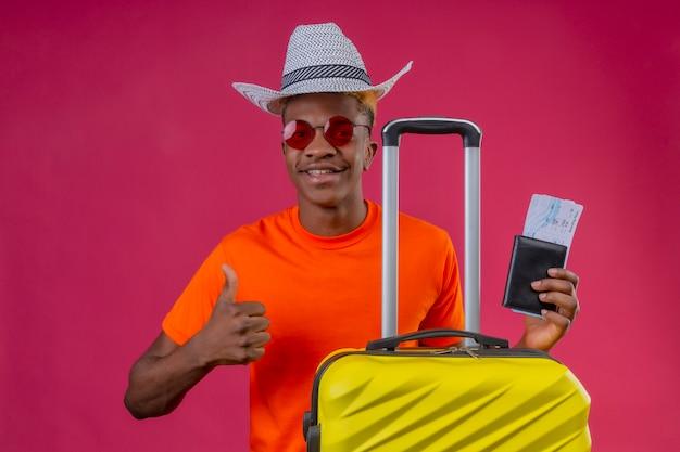Jonge afro-amerikaanse reiziger jongen dragen oranje t-shirt en zomer hoed houden reiskoffer en vliegtickets kijken camera glimlachend positief en gelukkig duimen opdagen op roze achtergrond